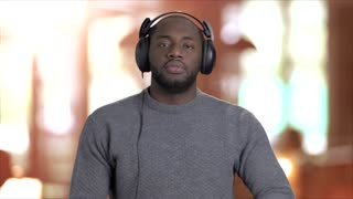 Energetic man listening to music in headphones. Handsome afro-american guy in headphones dancing and giving thumbs up on blurred background.
