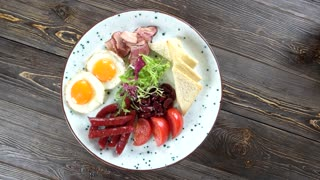 English breakfast with lettuce. Tasty dish on wooden background.