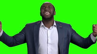 Excited afro american businessman with clenched fists. Joyful afro american entrepreneur celebrating victory on Alpha Channel background, slow motion.