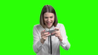 Excited girl playing video games on smartphone. Green screen hromakey background for keying.