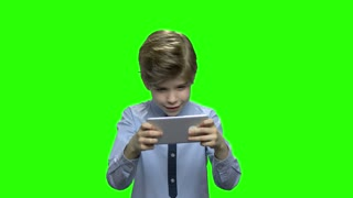 Excited kid playing game on smartphone. Green hromakey background for keying.