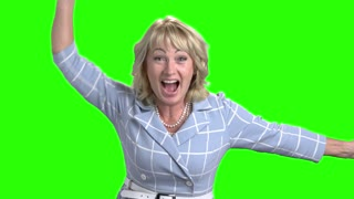 Excited mature woman on green screen. Joyful woman raised hands in excitement on chroma key background. Middle-aged woman triumphing victory.