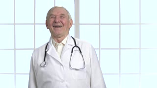 Experienced old senior doctor with stethoscope. Laughing hard, very funny. Bright checkered framed windows background.