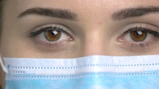 Extreme close up brown eyes with medical mask. Brown-eyed female doctor eyes.