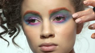 Eyeshadow applying, young model. Colorful artistic makeup.