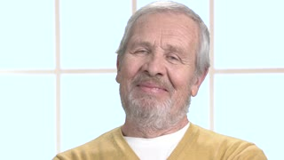 Face of bearded elderly man close up. Positive smiling grandfather close up. Human facial expressions.