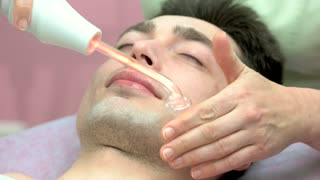 Face of beauty clinic customer. Man having darsonval therapy. Implementing new technologies in medicine.