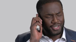 Face of black businessman talking on phone. Handsome afro-american manager using mobile phone and smiling on grey background close up.