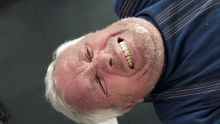 Face of elderly man lifting weights. Senior grey haired man doing heavy weight exercise for chest with barbell in gym.