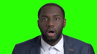 Face of shocked man on green screen. Afro american businessman looking shocked and worried on chroma key background. Human expressions of shock.