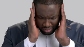 Face of sick businessman close up. Afro-american manager suffering from strong headache on grey background. Human expression of pain.