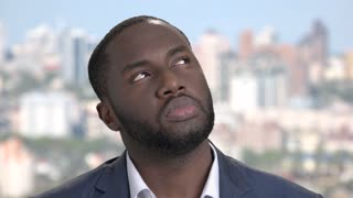 Face of upset afro-american businessman. Close up thoughtful african-american entrepreneur looking sad on blurred background. Bad memories concept.