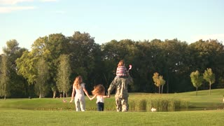 Family and soldier in a military uniform walking away, slow motion. Father holds daughter on shoulders, back view.