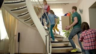Family carrying boxes upstairs. Group of people indoors. Moving to a new place.