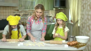Family cooking pastry. Girl rolling dough.