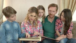 Family looks at photo album. Parents and children smiling indoor.