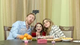 Family of three taking selfie. Table with food and present. Humble birthday party at home.