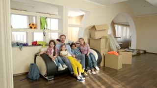 Family showing thumbs up indoor. Happy people and carboard boxes. How to win a house.