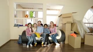 Family showing thumbs up indoors. Joyful people and carboard boxes. Benefits of mortgage.