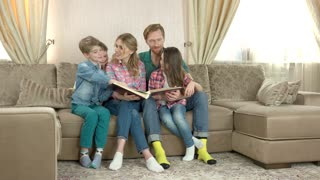 Family with a book. Adults and children indoors. Advice on home schooling.