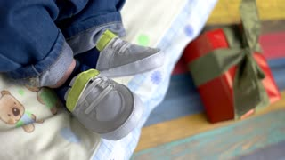 Feet of baby in sneakers. Little child wearing shoes. Born to be stylish.