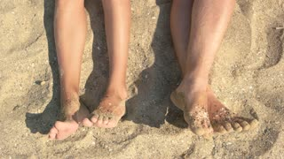 Feet of couple and sand. Male and female legs, beach.