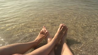 Feet of couple in slow-mo. Legs on seashore.