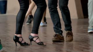 Feet of people dancing on a club party. Unrecognizable. Wooden floor background.