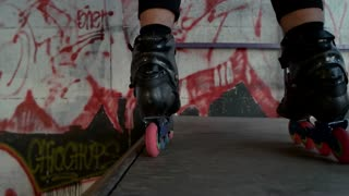 Feet of rollerbladers in slow-mo. Inline skates and ramp. Sports equipment advertising.