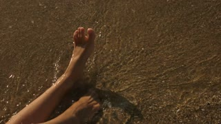 Feet of woman on seashore. Legs, sand and water.