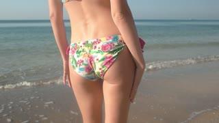 Female body dancing in slow-mo. Woman in bikini near sea.