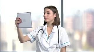 Female doctor using computer tablet. Young happy medical worker holding pc tablet and waving with hand. People, communication, technology.