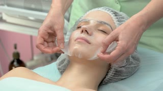 Female face after hydrogel mask. Hands of a cosmetician working. How collagen affects skin.