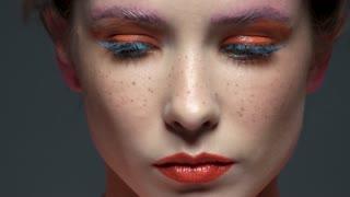 Female face, beautiful artistic makeup. Serious woman close up.