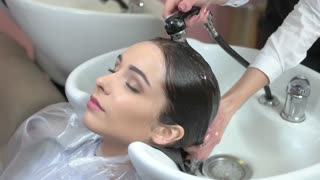 Female getting her hair washed. Beauty salon client, closed eyes. Hair restoration products.