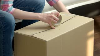 Female hands packing box. Woman with marker writing.