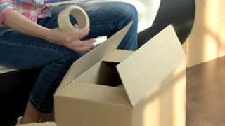 Female hands quickly packing box. Woman writing with marker. Time saving tips for moving.