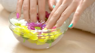 Female hands receiving spa procedure. Female fingernails soaking in hand bath. Beautiful young woman hands with summer design nails in spa salon.