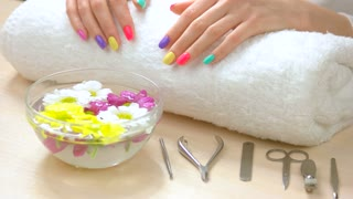 Female hands receiving spa treatment. Female hands with fresh summer manicure on white towel afte spa. Skin care and spa therapy.
