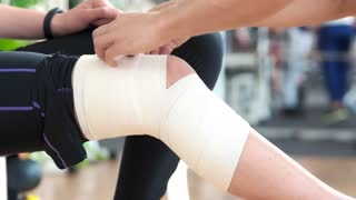 Female leg wrapped with medical bandage. Male hands fixed elastic bandage on girls injured leg at gym. Sport and health.