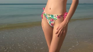 Female legs dancing on seashore. Body of a slim woman. Be free and sexy.