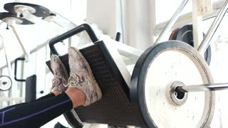 Female legs training on machine press in gym. Woman doing strength training on a gym close up.