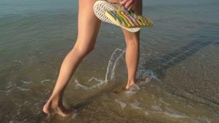 Female legs walking on seashore. Young woman carrying flip flops.