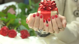 Female manicured hands with gift box. Handmade gift box with red box in senior woman manicured hands. Birthday celebration concept.