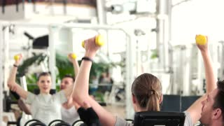 Female person working out at gym. Male fitness instructor helping to client exercising with dumbbells at gym. People, sport and lifestyle.