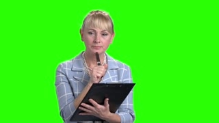 Female supervisor with black clipboard. Elegant mature woman making note on clipboard on chroma key background. Inspection and documentation.