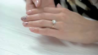 Female well-groomed hands with ring. Young woman hands with beautiful manicure wearing luxury ring with diamond. Woman demonstrating expensive ring with precious stone.