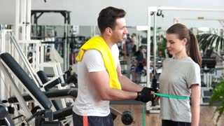 Fitness trainer measuring waist of female client. Personal trainer measuring progress in training of client. Satisfied woman expressing her success at gym. Sport and diet concept.