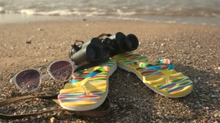 Flip flops and binoculars. Sunglasses on seashore. Explore new horizons.