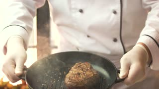 Flipping steak in slow motion. Chef with a frying pan. Learn to cook with professionals.